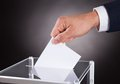 Businessman inserting ballot in box on desk cropped image of against black background Stock Photos