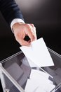 Businessman inserting ballot in box on desk cropped image of against black background Royalty Free Stock Photography