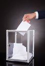 Businessman inserting ballot in box on desk cropped image of against black background Stock Image