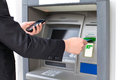 Businessman inserts a credit card into the atm to withdraw money and holding phone Stock Photo