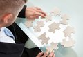 Businessman with a jigsaw puzzle spread out on his desk trying to match the pieces in concept of problem solving and meeting Stock Image