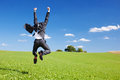 Businessman jumping for joy celebrating a successful achievement in a lush green field under a blue sky Royalty Free Stock Image