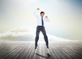Businessman jumping over wooden boards leading out to the horizon with his fist in the air Royalty Free Stock Images