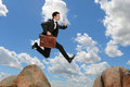 Businessman jumping from rock with briefcase to with clouds in background Royalty Free Stock Images