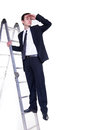 Businessman on ladder searching for possibilities young a Stock Photo