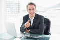 Businessman with laptop gesturing thumbs up at office desk portrait of a smiling young Royalty Free Stock Images