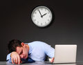 Businessman with laptop tired is sleeping at his table Stock Photos
