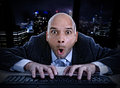 Businessman late at night in office typing on computer keyboard with funny face expression on watching porn online Royalty Free Stock Photo