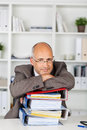 Businessman leaning with folded arms on binders a stack of Stock Image