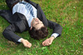 Businessman lies on back on grass Stock Images
