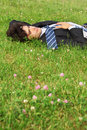 Businessman lies on back on grass with closed eyes Stock Image