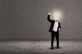 Businessman with lightbulb head raised arm on grey background Royalty Free Stock Photography