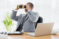 Businessman looking through binoculars at desk serious young office Royalty Free Stock Photo