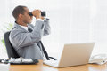 Businessman looking through binoculars at office desk Royalty Free Stock Images