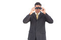 Businessman looking at the camera with binoculars and wearing a suit Royalty Free Stock Photography