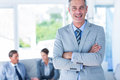 Businessman looking at camera with his colleagues behind him in office Royalty Free Stock Image