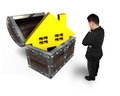 Businessman looking at golden house in treasure chest Royalty Free Stock Photo
