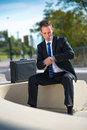 Businessman looking at his watch while sitting in the park successful Royalty Free Stock Image