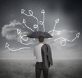 Businessman looking at jumble up arrows holding umbrella in dark grey landscape Stock Photos