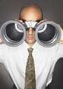 Businessman looking through large binoculars closeup of a bald against gray background Stock Photos