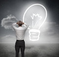 Businessman looking at light bulb with hands on head in dark grey landscape Royalty Free Stock Images