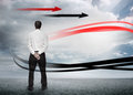 Businessman looking at red and black arrows in cloudy landscape Royalty Free Stock Images