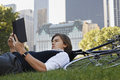 Businessman lying down on bicycle while reading book side view of young in park Stock Image
