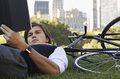Businessman lying down on bicycle while reading book young in park Stock Photos