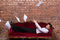 Businessman lying on a settee with flying papers conceptual image of an elegant relaxing against brick wall paperwork floating in Royalty Free Stock Images