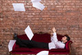 Businessman lying on a settee with flying papers conceptual image of an elegant relaxing against brick wall paperwork floating in Royalty Free Stock Photos