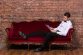 Businessman lying on a settee and reading paperwork conceptual image of an elegant relaxing against brick wall Royalty Free Stock Photo