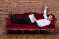 Businessman lying on a settee and reading paperwork conceptual image of an elegant relaxing against brick wall Royalty Free Stock Photos