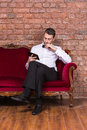 Businessman lying on a settee and reading tablet conceptual image of an elegant relaxing against brick wall Stock Photos