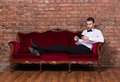 Businessman lying on a settee and reading tablet conceptual image of an elegant relaxing against brick wall Royalty Free Stock Photo