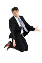 Businessman making an imploring gesture impassioned with outstretched arms while either kneeling on the floor or leaping in the Royalty Free Stock Image
