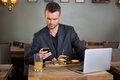 Businessman messaging on cellphone while having young text sandwich in coffee shop Royalty Free Stock Photography