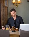 Businessman messaging on mobilephone while having young text mobile phone meal at cafe Stock Photo