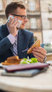 Businessman with mobile phone during breakfast Royalty Free Stock Photo