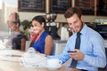 Businessman with mobile phone and newspaper in coffee shop smiling Stock Images