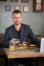 Businessman with mobilephone and laptop having portrait of confident sandwich in coffeeshop Stock Images