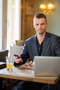 Businessman with mobilephone and laptop having portrait of young food in cafe Royalty Free Stock Photos