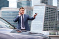 Businessman near a car on background of office the gives instructions over the phone and shows the hand Stock Photo