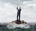 Businessman needs help standing on lonely rock in sea is getting in business concept Royalty Free Stock Image