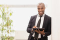 Businessman with note pad cheerful young african writing something in his and smiling at camera Royalty Free Stock Photos