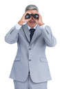Businessman observing through binoculars on white background Royalty Free Stock Image