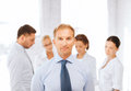 Businessman in office with group on the back business school and education concept smiling handsome team Stock Images