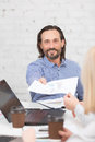 Businessman in office happy giving sheet of paper to his colleague happy bearded man smiling for camera while working Royalty Free Stock Photography