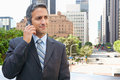 Businessman outside office on mobile phone chatting Stock Photos