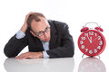 Businessman overworked with red clock isolated on white backgrou background Stock Image