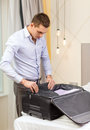 Businessman packing things in suitcase business technology internet and hotel concept happy hotel room Royalty Free Stock Photo